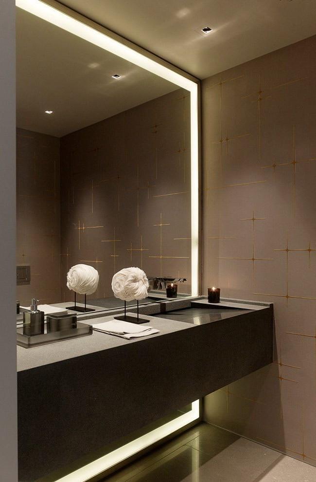 Подсветка по периметру большого зеркала в сочетании с приглушенным верхним светом создают ощущение интимности, как раз для вечернего туалета