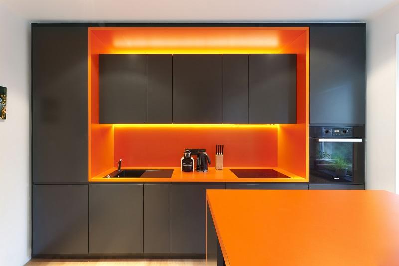Системы вытяжек, фартуки и фасады с подсветкой станут отличным дополнением к оранжево-черной стилистике кухни