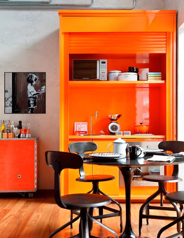 Продуманно организованная и компактная кухня с доминирующим оранжевым в отделке