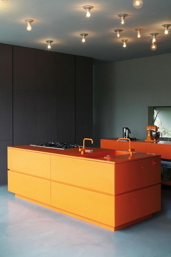 Полностью оранжевый кухонный остров в темном интерьере
