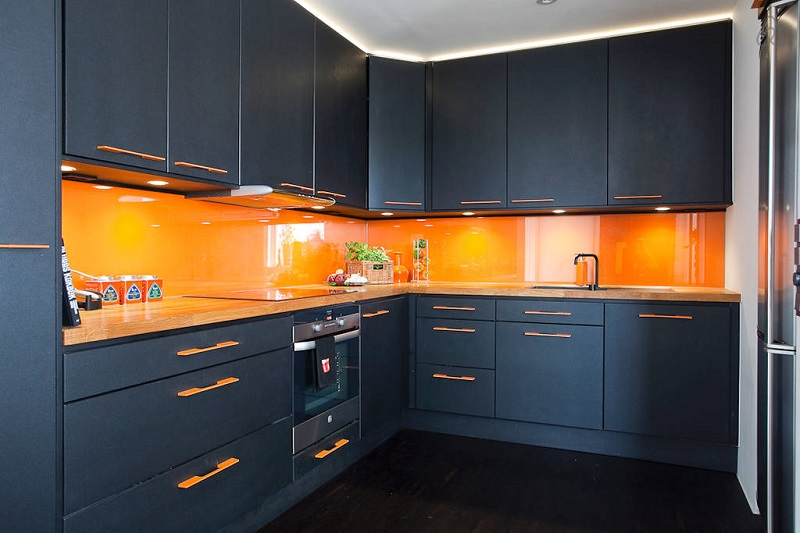 Темно-синие или же черные кухонные фасады отлично оттенят интенсивный оранжевый