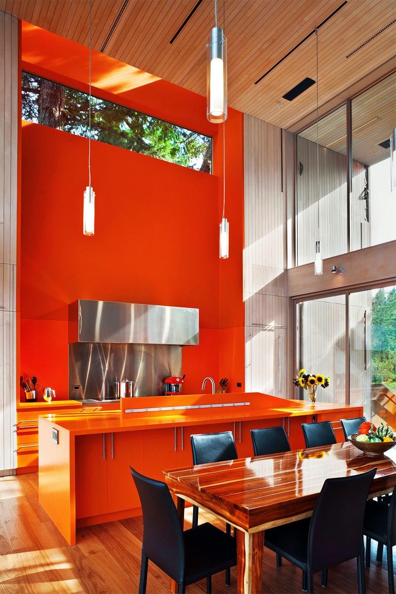 Обилие оранжевого в сочетании с теплыми оттенками дерева на полу и потолке