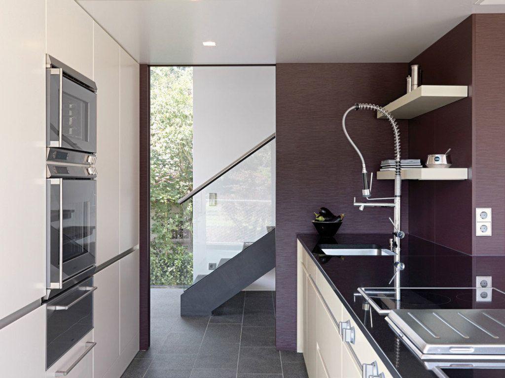Благодаря всей отражающей способности, черная столешница лучше вписывается в фиолетовое окружение кухни