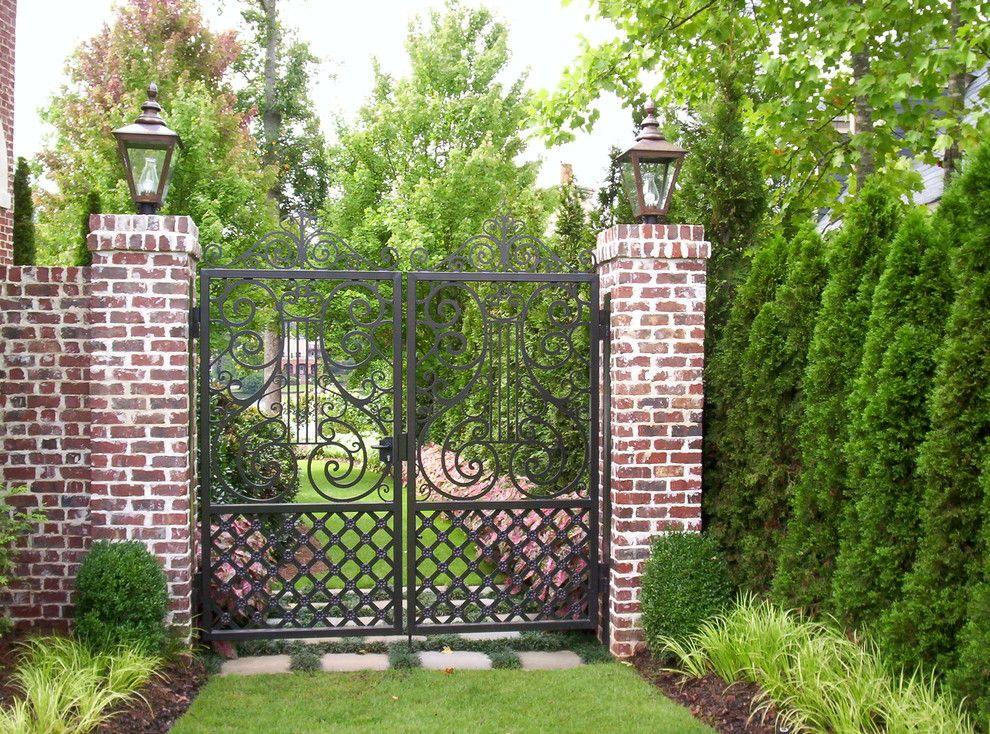 Кованые ворота отлично сочетаются с голой кирпичной стеной