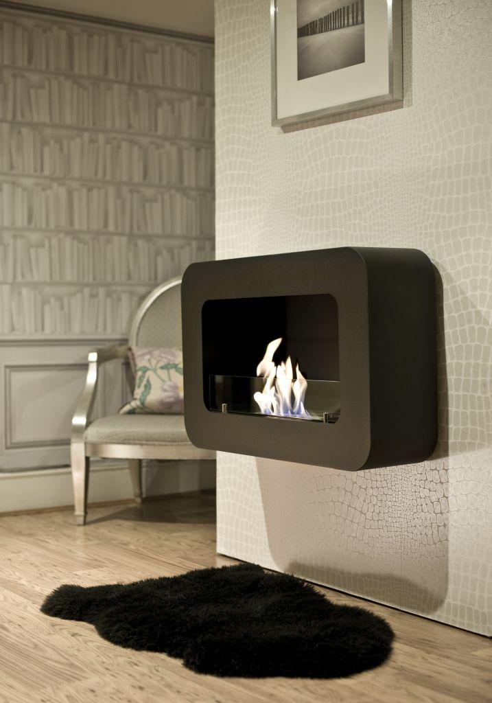 На фоне бело-серебряной стены удачным контрастом смотрится черный навесной камин со скругленными углами.