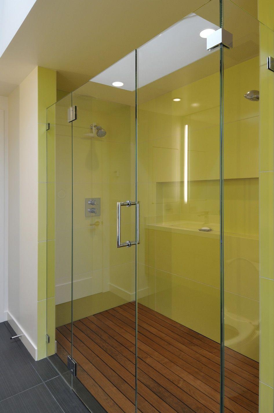 Стены душа сочного лимонного цвета отлично просматриваются сквозь стеклянную дверь