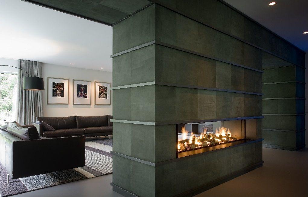 Камин, что внутри перегородки, облегчает конструкцию. Такое его размещение дает возможность наслаждаться живым огнем с двух сторон.