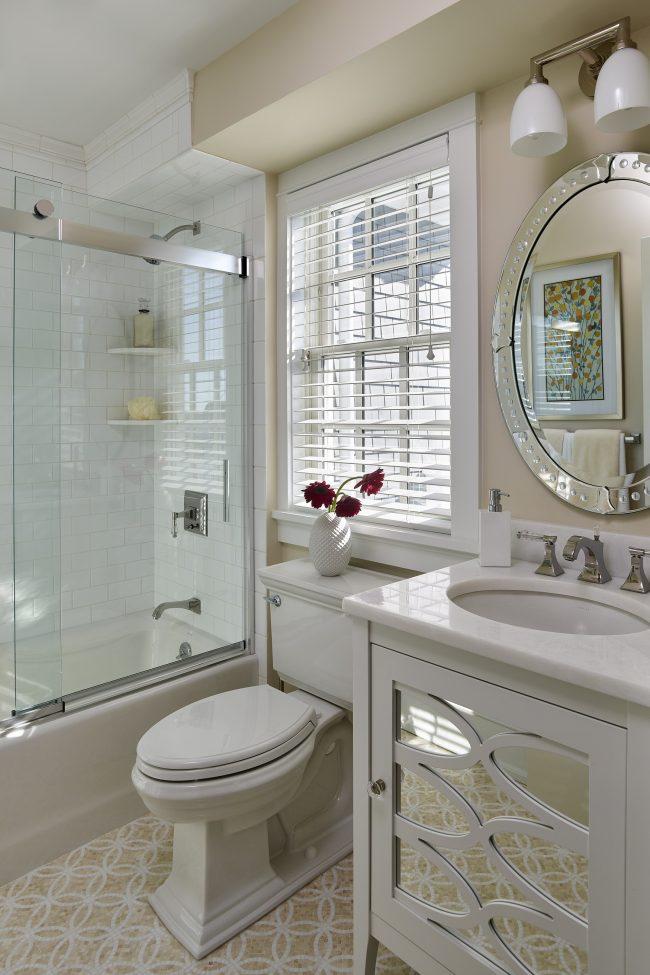 Надежно закрепленная металлическими пластинами стеклянная раздвижная шторка в светлой ванной