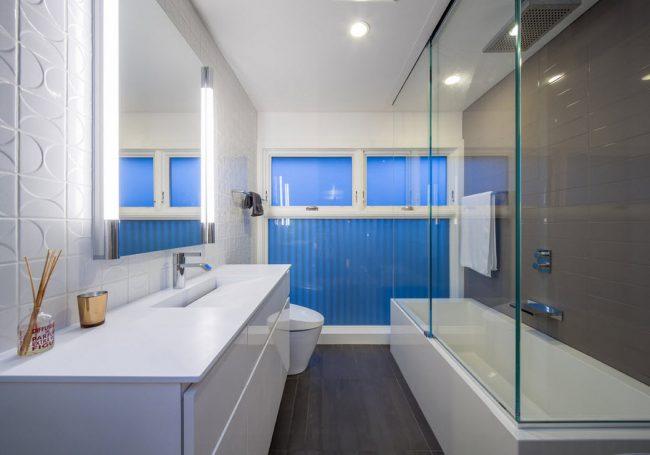 Просторная ванная комната с большой стеклянной шторкой и яркими синими цветовыми акцентами