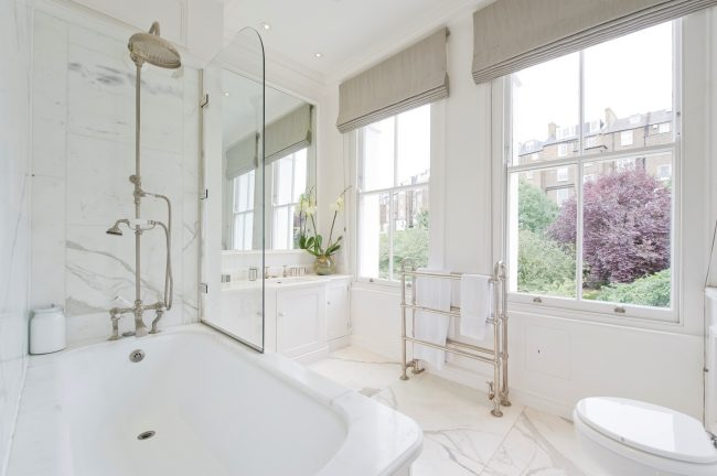 Стеклянное полотно в нежной ванной в белых тонах и легкими римскими шторами на окнах