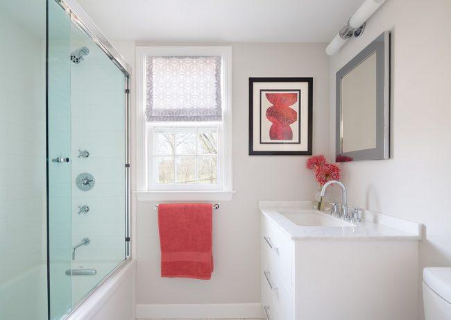 Очень аккуратная ванная комната с легкой стеклянной раздвижной шторкой и нежными розовыми акцентами на элементах декора