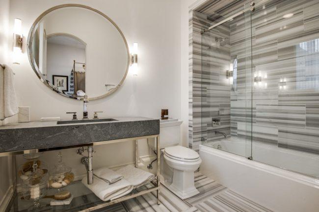 Изысканная комната с открывающейся стеклянной шторкой и необычной, но в то же время выдержанной в строгой цветовой гамме отделкой пола и зоны у ванной
