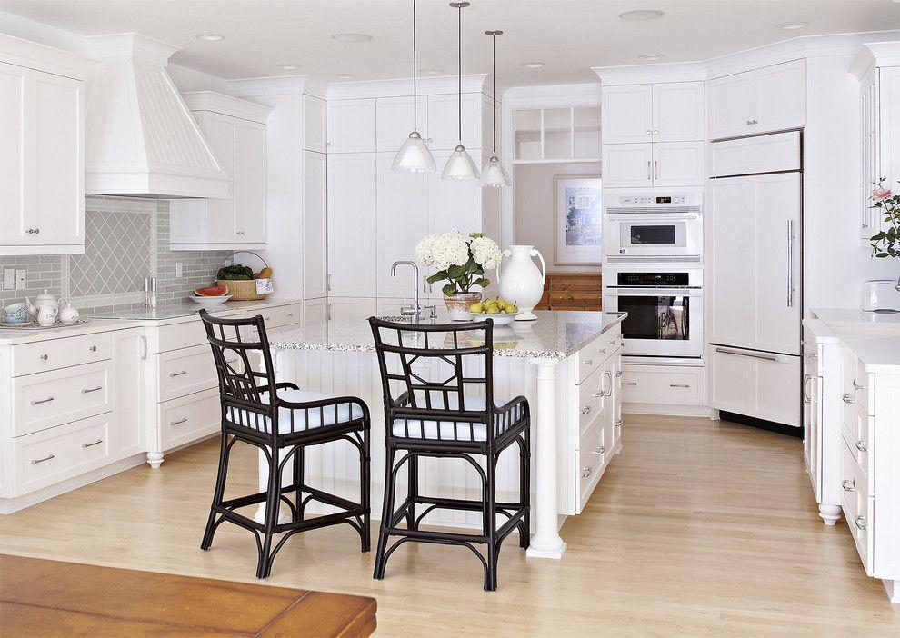 Просторная белая кухня с встроенным в угол холодильником