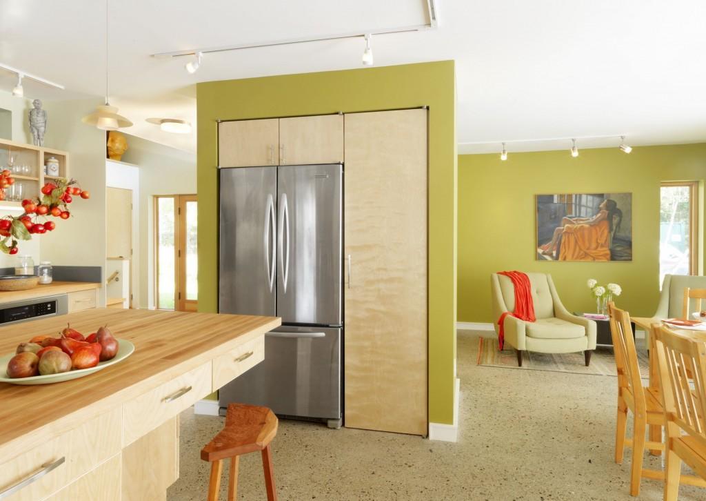 В квартире-студии холодильник, встроенный в небольшую стену, не только обеспечивает комфортность пребывания на кухне, но и служит элементом зонирования помещения