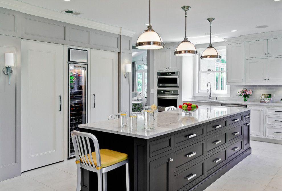 В пространстве большой кухни выделили отдельную стену для размещения холодильной техники, спрятав ее за белыми мебельными фасадами