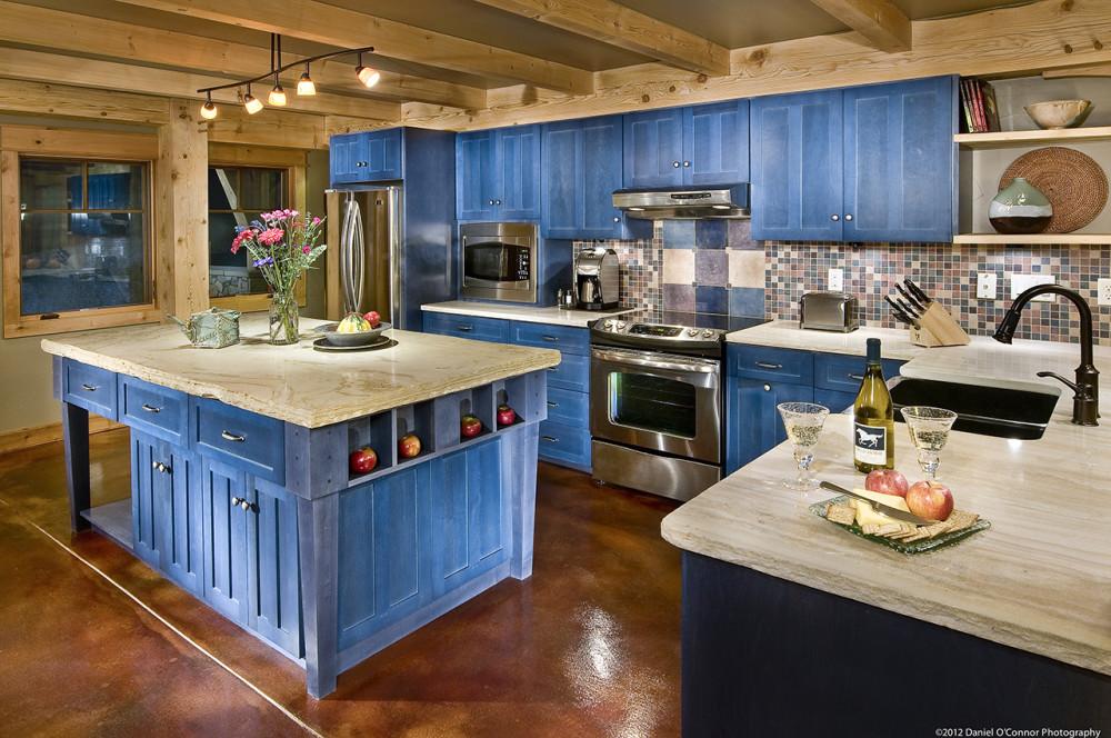 Дизайн кухни выполненный в дереве с крашеными фасадами в приятный синий цвет - необычное решение. Холодильник занял свое место в углу возле окна