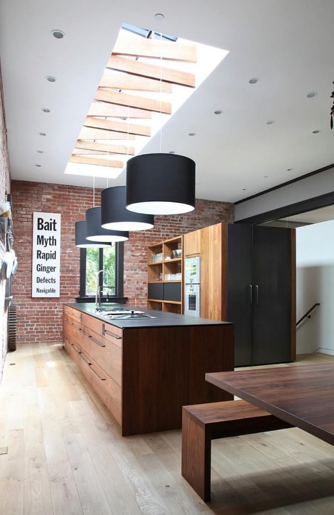 Нетрадиционная планировка кухонной зоны в стиле лофт, где в торце шкафов за темно-серыми фасадами скрывается холодильник