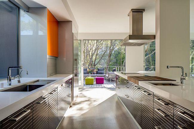 Если привычное серое оформление кухни в стиле техно кажется скучным, всегда можно разбавить интерьер яркими деталями. Например, шкафчиками или пуфиками вызывающих тонов