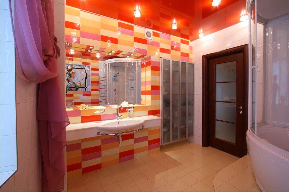 Чтобы поддержать ярко красный глянцевый потолок, отделку одной стены в помещении можно выполнить яркой плиткой с краснымы элементами
