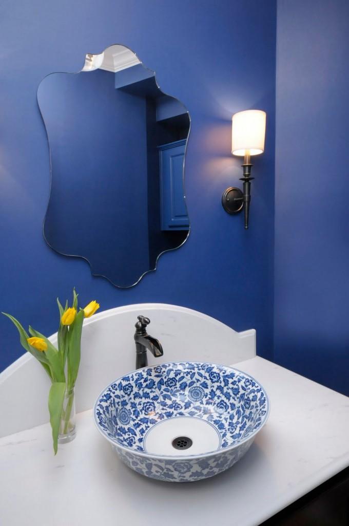 Расписанная цветочным узором чаша контрастно смотрится на фоне однотонных синих стен