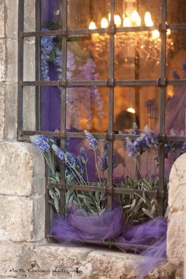 Грубость массивной кованой решетки смягчают нежные цветы и ткань - оригинальный и очень красивый декор окна