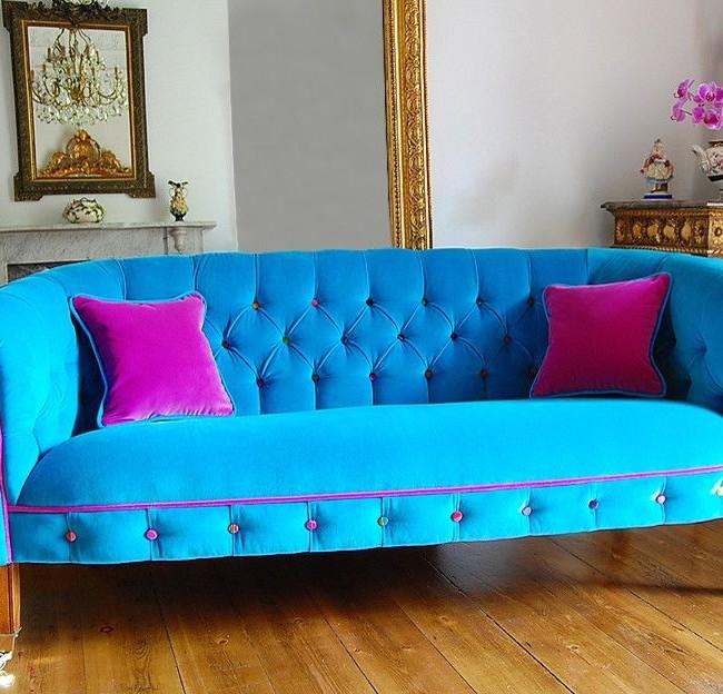 Ярко-голубая софа с фиолетовыми подушками