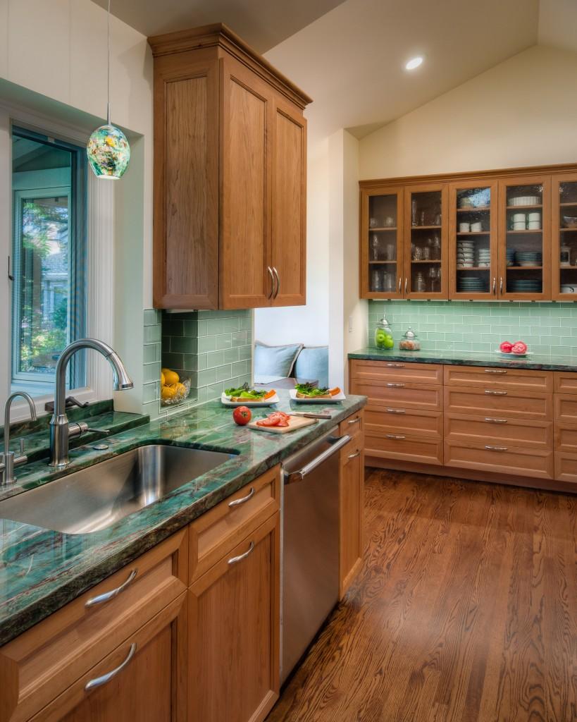Малахитовый цвет столешницы хорошо сочетается с фасадами кухни, выполненными с дерева