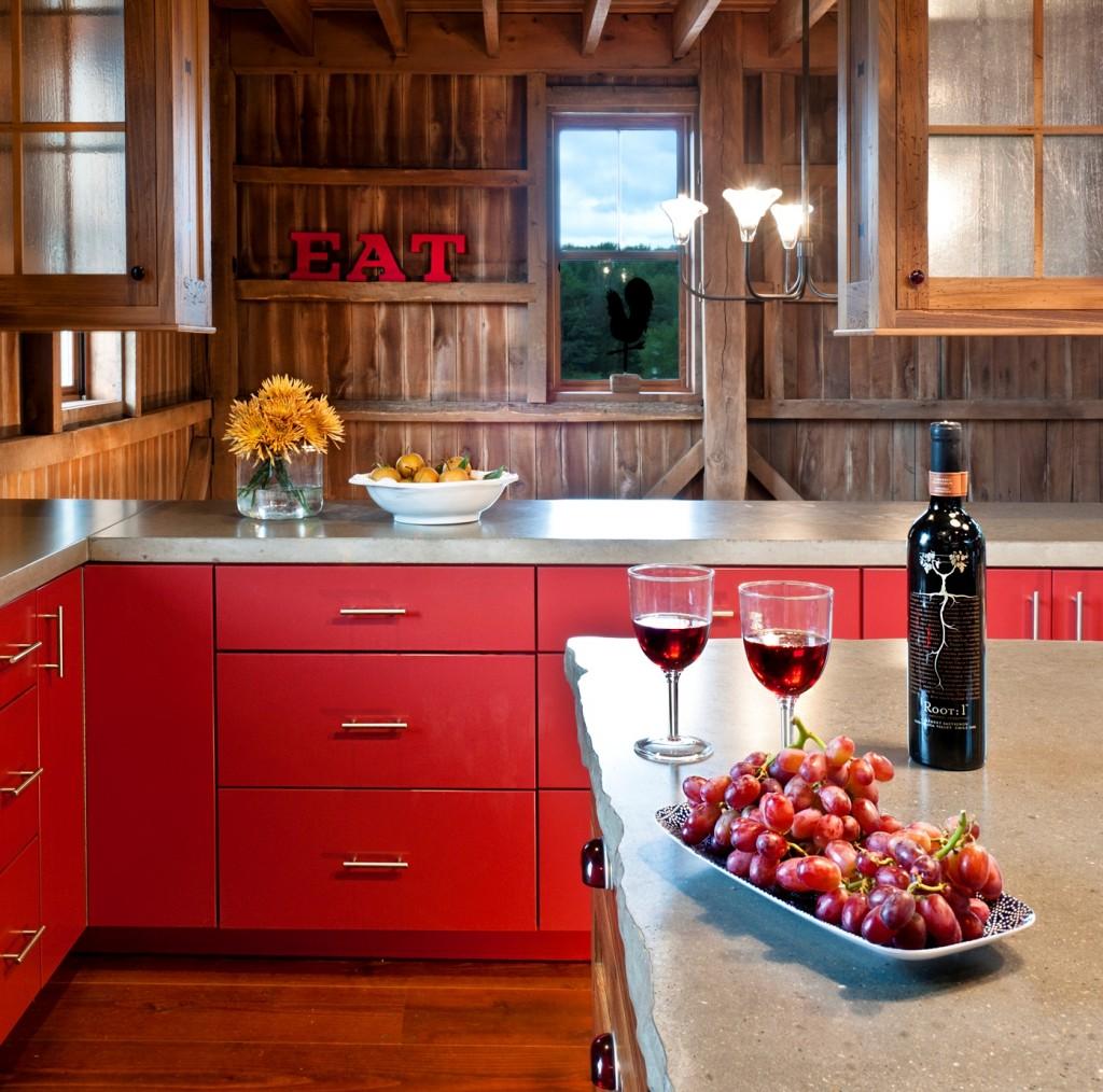 Серая столешница из камня удачно сочетается с деревом и красным цветом кухонного гарнитура