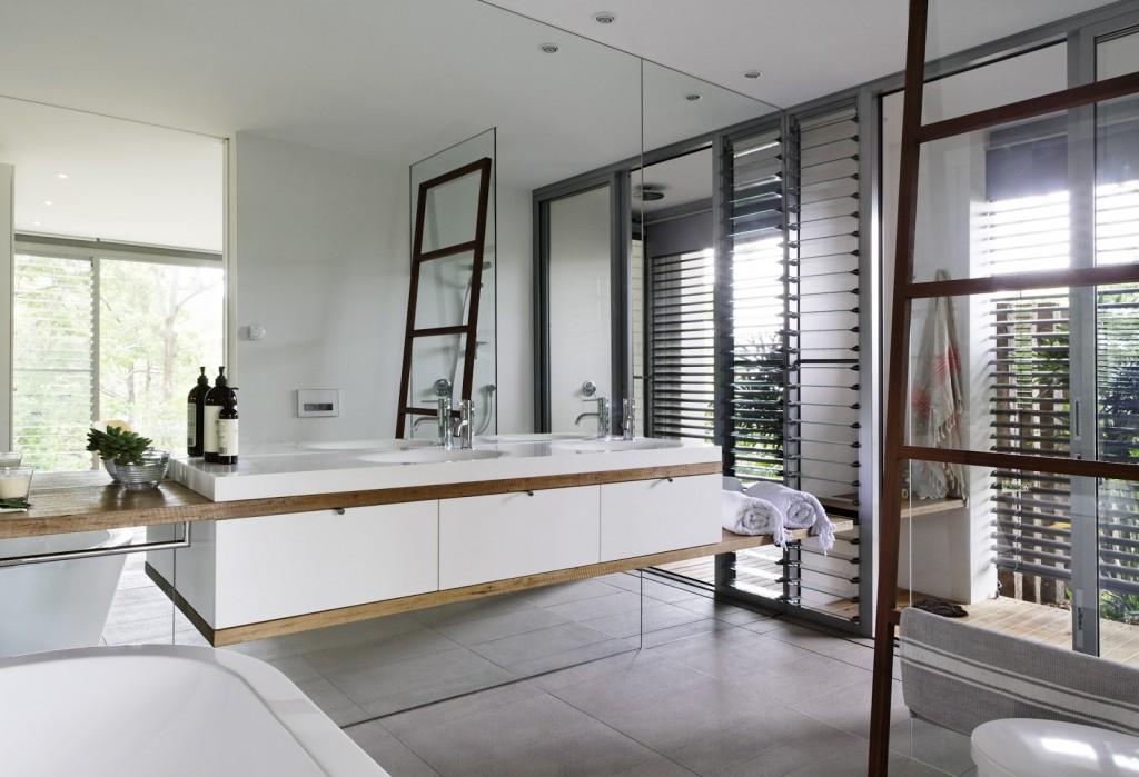Длинная белая тумба с элементами дерева подчеркивает линейный характер дизайна данной ванной комнаты