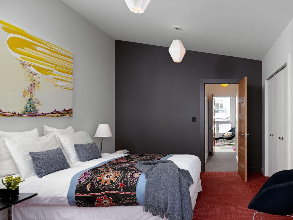 Эффектное цветовое сочетание черной стены и красного ковролина в спальне
