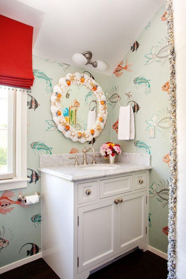 Ванная с морской тематикой и мягкими пастельными обоями с графическим изображением разных видов рыб. Зеркало из ракушек ручной работы – особенность интерьера