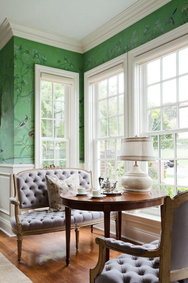 Традиционная американская столовая: узкие высокие окна с римскими шторами, элегантные диваны, лакированный деревянный стол и зеленые обои с рисунком