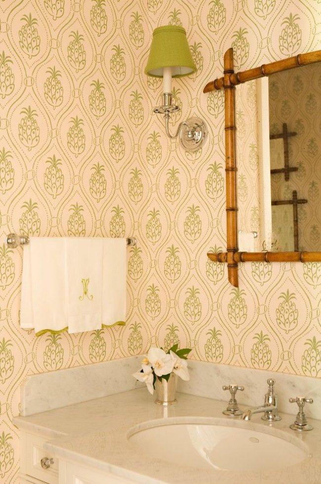 Эклектичная ванная с принтом зеленого цвета в виде ананаса и бамбуковой рамой для зеркала подчеркивают тропическую тематику оформления интерьера