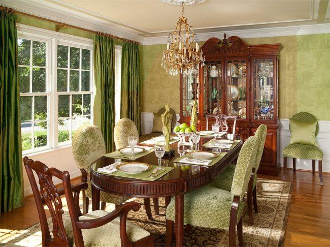 Классический интерьер столовой комнаты с резной деревянной мебелью, атласными шторами и подушками, скульптурами, люстрой золотого цвета и другими роскошными интерьерными элементами