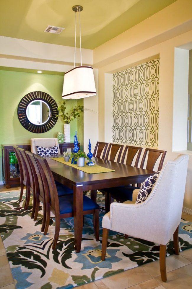Одна из стен столовой окрашена в светло-салатовый оттенок, вторая имеет сложный повторяющийся геометрический рисунок, а потолок окрашен в теплый зеленый оттенок – оригинальное решение в оформлении современного интерьера