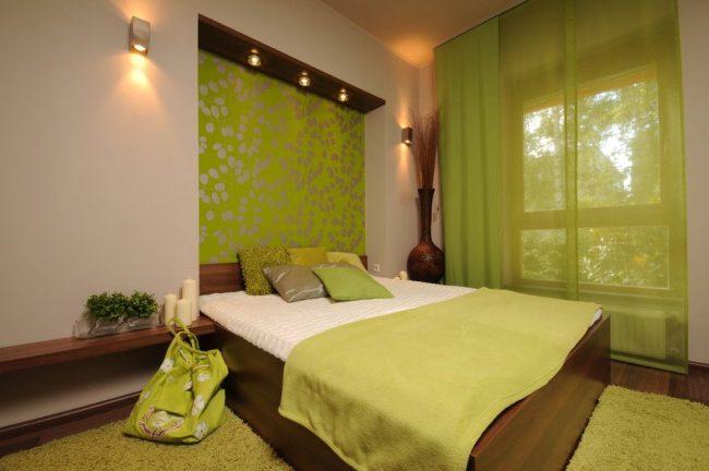 Темное дерево в оформлении мебели и пола, панно над кроватью цвета зеленого яблока, подушки разных оттенков зеленого и другие элементы интерьера, подчеркивающие классическое сочетание зеленого с коричневым в интерьере