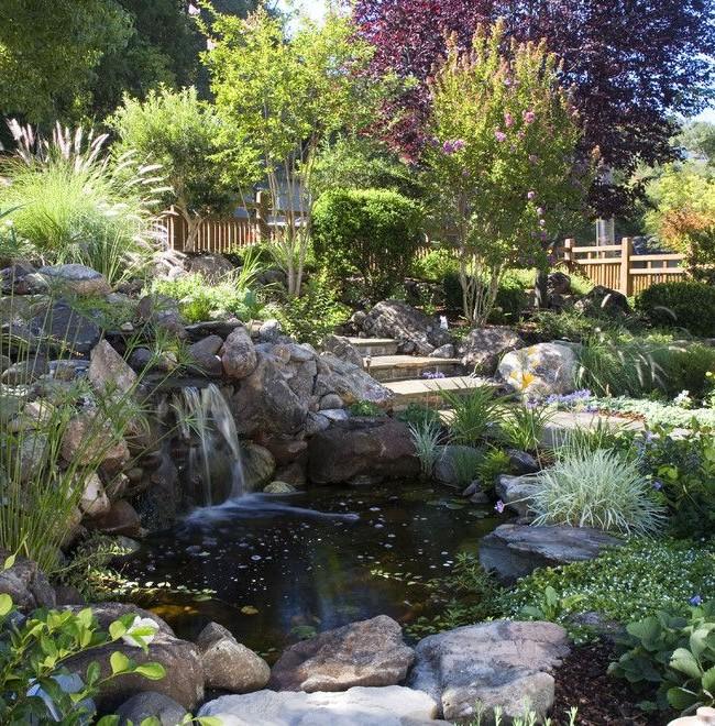 Водоем, окруженный камнями, с водопадом в зеленом саду