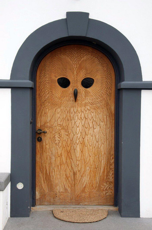 Наружная деревянная дверь украшенная резным рисунком совы