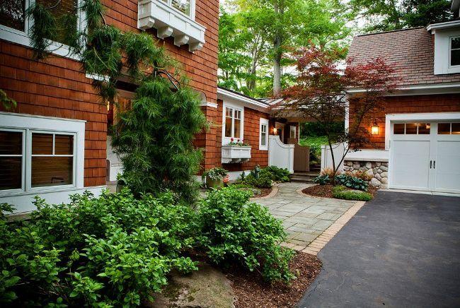 Дом украшен зеленой красивой лиственницей