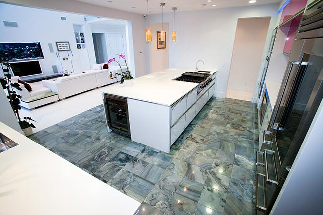Плиты из натурального полированного камня на кухонном полу смотрятся очень солидно