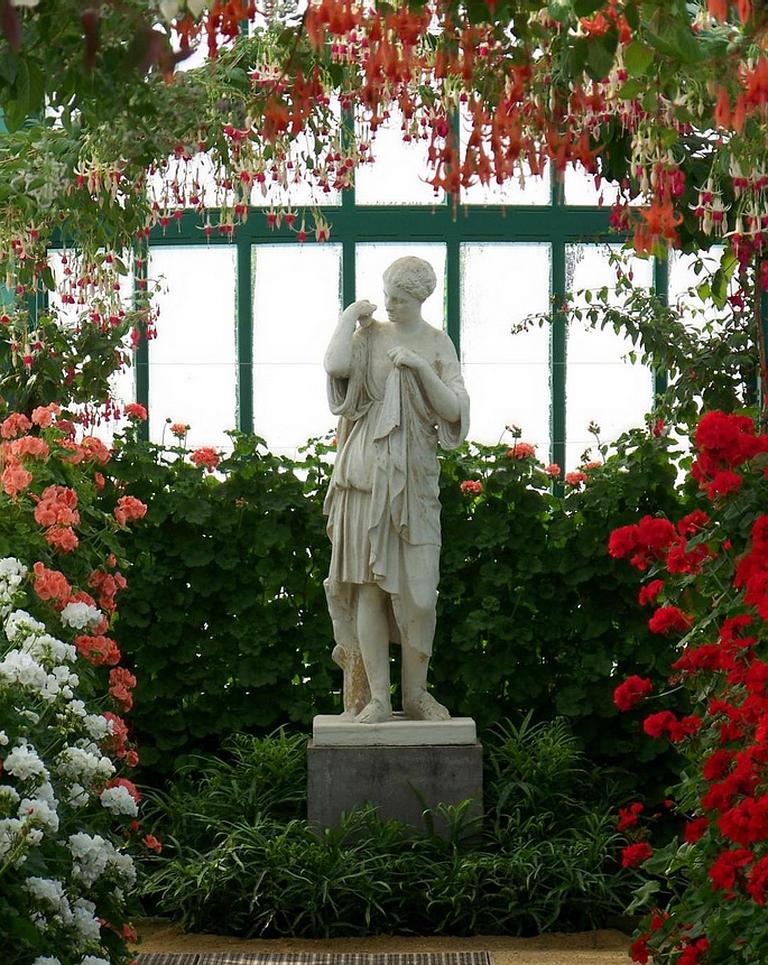 Хорошая композиция из цветов и декоративных элементов значительно украсит сад-оранжерею