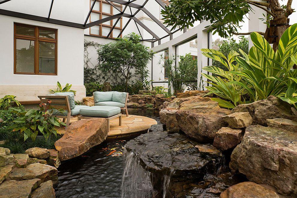 Пруд с рыбами и искусственный водопад в зимнем саду
