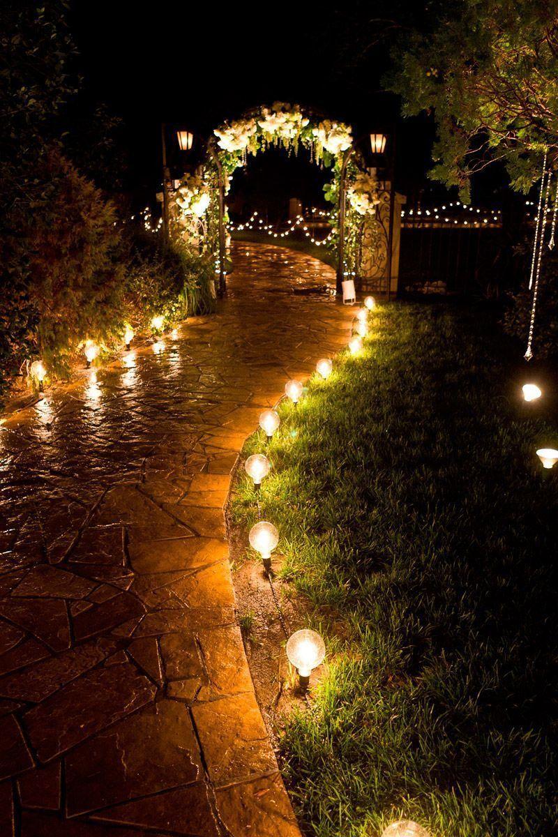 Цепочка светильников выставлена вдоль садовой дорожки