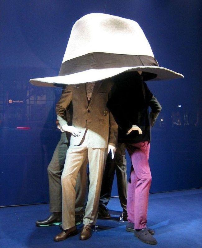 Три манекена под огромной шляпой - на витрине магазина мужской одежды