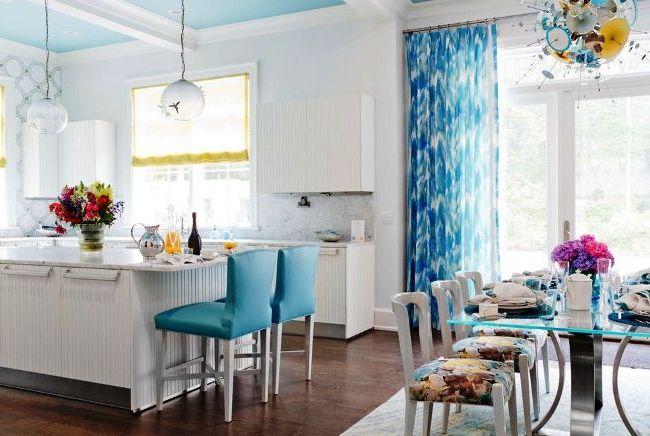 Комбинация из римской желтой шторы и шифоновых голубых занавесок придает кухне легкий романтичный дух