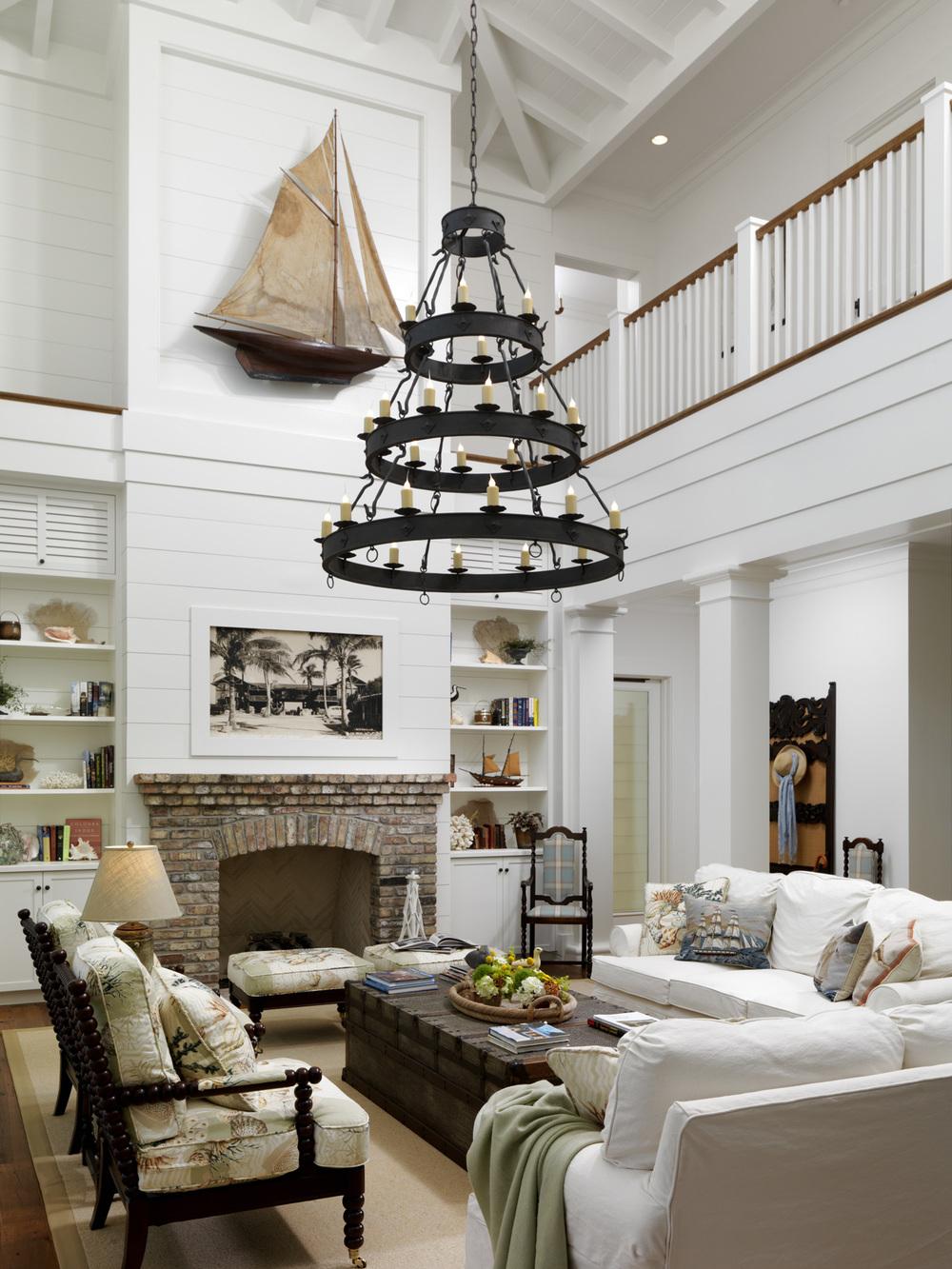 Для гостиной с высоким потоком удачное решение - многоуровневая кованая люстра с лампочками-свечками