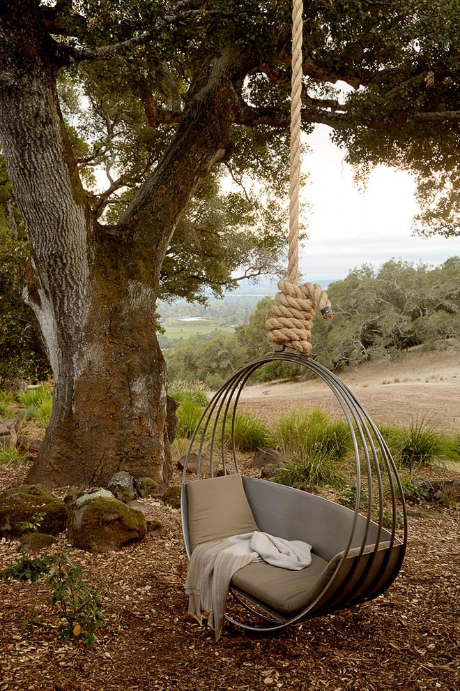 Подвесная качеля, сидение которой выполнено с металлических колец, станет настоящим украшением вашего двора