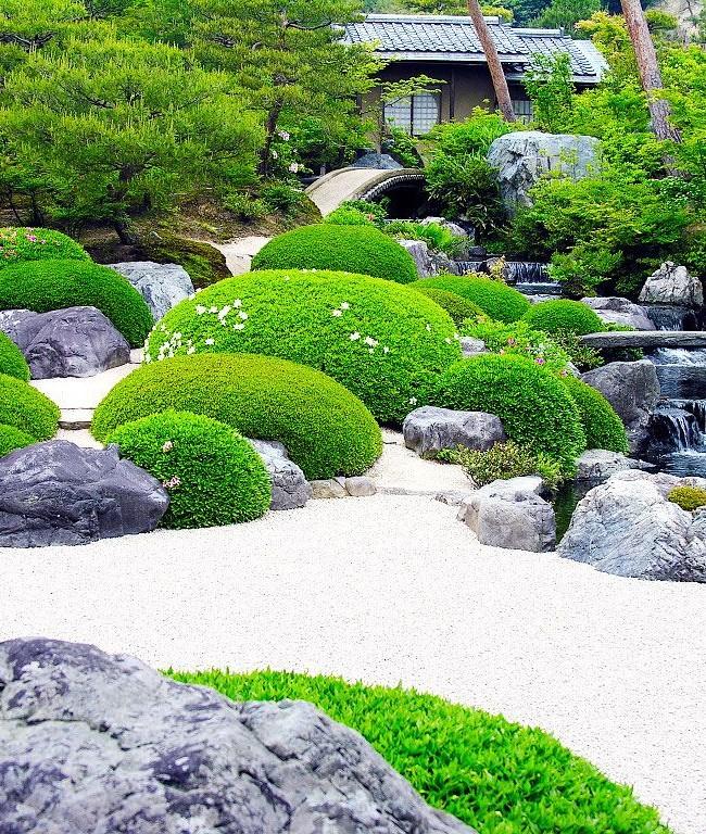 Роскошная зелень насаждений выглядит очень красиво на фоне белого гравия и каменистого водопада