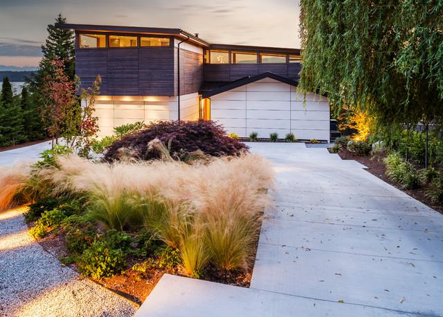 Дорожка к дому, усыпанная гравием, и подъезд к гаражу очень гармонично вписались в ландшафтный дизайн