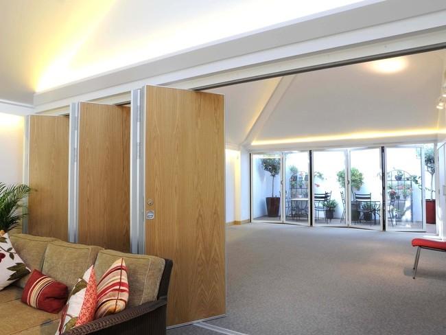 Две перегородки-гармошки - из стекла и дерева - в одном помещении